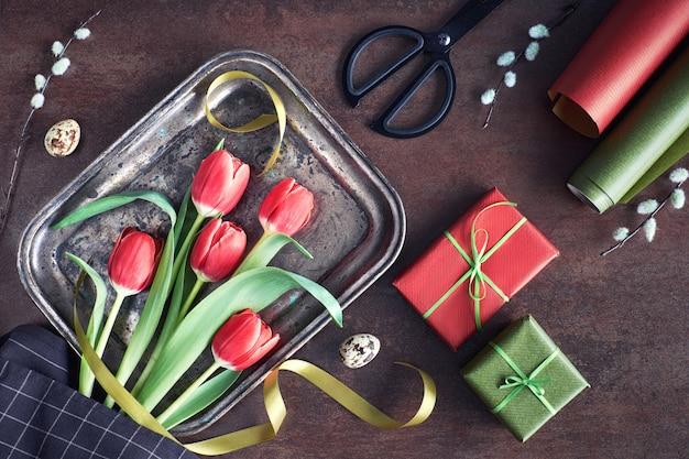 Zasięrzutny widok wiosennych dekoracji: zawinięte prezenty, kwiaty wierzby i tulipanów na ciemnym tle Premium Zdjęcia
