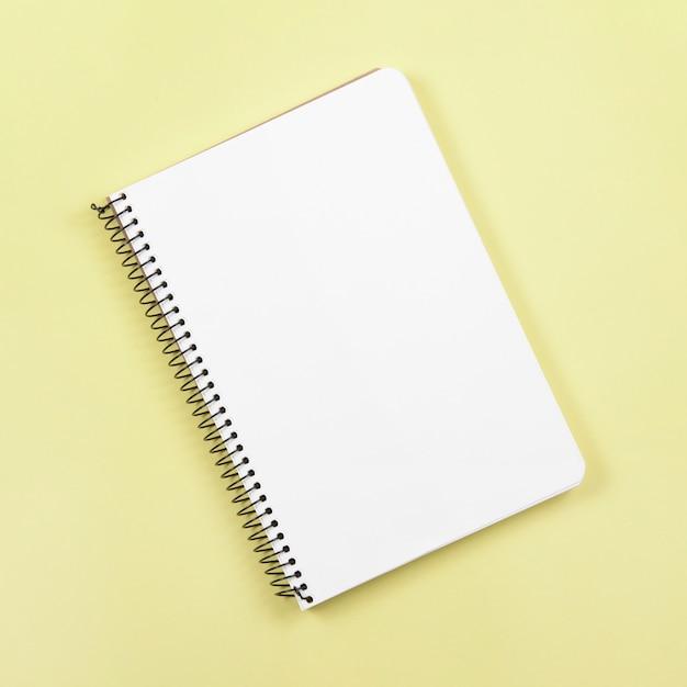 Zasięrzutny widok zamknięty ślimakowaty notatnik na żółtym tle Darmowe Zdjęcia