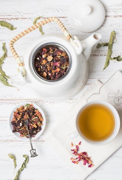 Zasięrzutny Widok Ziołowa Herbata Z Wysuszonymi Różanymi Płatkami Na Drewnianym Biurku Darmowe Zdjęcia