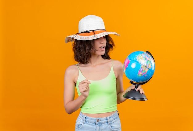 Zaskakująca Młoda Kobieta Z Krótkimi Włosami W Zielonej Bluzce, W Kapeluszu Przeciwsłonecznym, Patrząc Na Kulę Ziemską Darmowe Zdjęcia