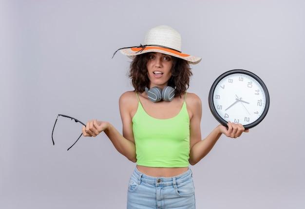 Zaskakująca Młoda Kobieta Z Krótkimi Włosami W Zielonej Bluzce W Słuchawkach Ubrana W Kapelusz Przeciwsłoneczny, Trzymając Okulary Przeciwsłoneczne I Zegar ścienny Na Białym Tle Darmowe Zdjęcia