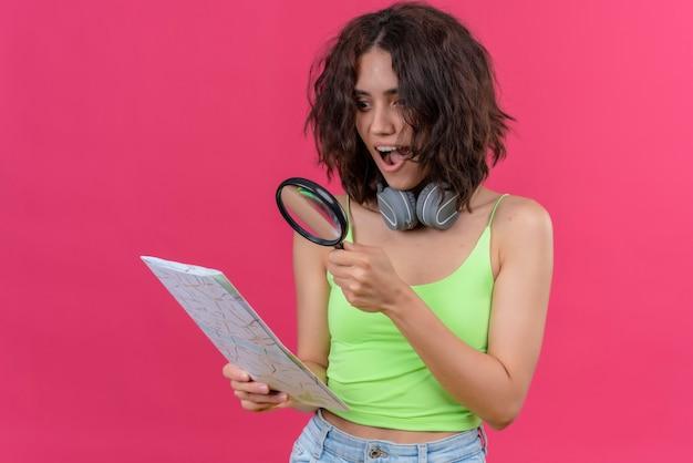 Zaskakująca Młoda ładna Kobieta Z Krótkimi Włosami W Zielonej Bluzce W Słuchawkach Patrząc Na Mapę Przez Lupę Darmowe Zdjęcia
