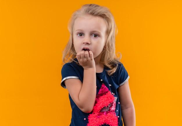 Zaskakująca Piękna Mała Dziewczynka O Blond Włosach W Granatowej Koszuli Trzymająca Rękę Na Brodzie Na Pomarańczowej ścianie Darmowe Zdjęcia