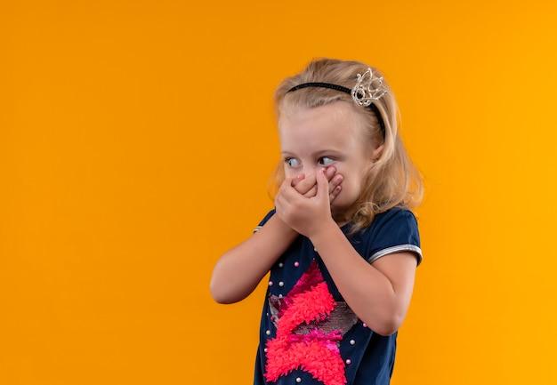 Zaskakująca śliczna Dziewczynka Ubrana W Granatową Koszulę Z Opaską W Kształcie Korony, Trzymająca Się Za Usta I Patrząc Z Boku Na Pomarańczową ścianę Darmowe Zdjęcia