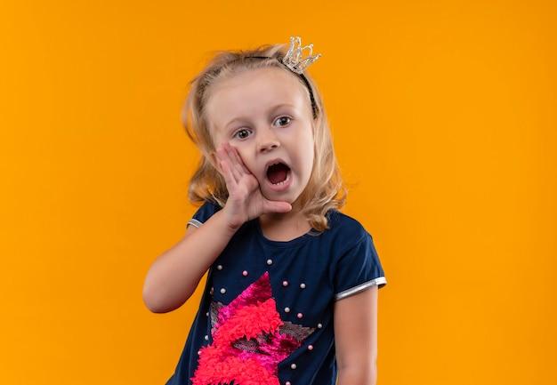 Zaskakująca, śliczna Dziewczynka W Granatowej Koszuli Z Opaską W Koronie Dzwoni Do Kogoś Z Rękami Na Ustach Na Pomarańczowej ścianie Darmowe Zdjęcia