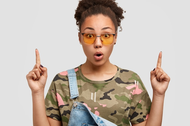 Zaskoczona Afroamerykanka W Modnych Odcieniach, Ubrana W Swobodny T-shirt W Kamuflaż I Dżinsowy Kombinezon, Wskazująca Palcami Wskazującymi W Górę Ma Zszokowany Wyraz Darmowe Zdjęcia