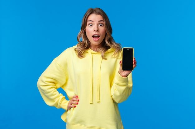 Zaskoczona I Zdziwiona śliczna Europejska Dziewczyna Pokazująca Niesamowitą Nową Aplikację Lub Grę Mobilną, Trzymająca Ekran Telefonu, Gapiąca Się Na Słowa Z Podniecenia, Niebieska ściana Premium Zdjęcia