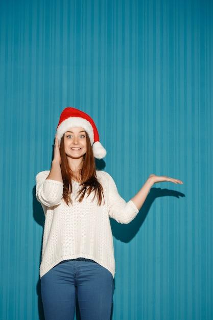 Zaskoczona Kobieta W Kapeluszu Santa Pokazując Z Prawej Strony Na Niebieskim Tle Darmowe Zdjęcia