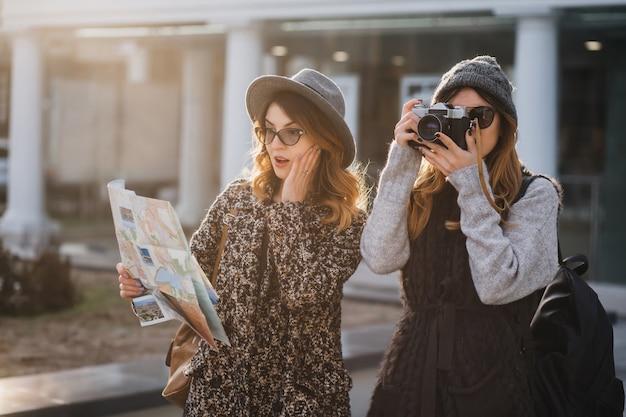 Zaskoczona Kręcona Kobieta W Okularach Patrząc Na Mapę, Dotykając Twarzy, Podczas Gdy Jej Przyjaciółka Robi Zdjęcia Zabytków. Atrakcyjna Podróżniczka Spacerująca Z Aparatem I Jej Siostra Szukająca Ciekawych Miejsc. Darmowe Zdjęcia