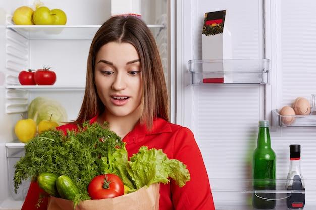 Zaskoczona Młoda Kobieta Ze Zdziwionym Wyrazem Twarzy Patrzy Na Warzywa, Zapomina Kupić Coś W Sklepie Spożywczym, Stoi W Kuchni Przy Lodówce. Premium Zdjęcia
