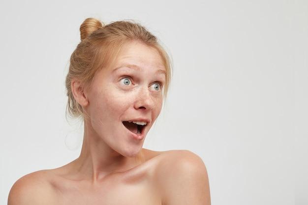 Zaskoczona Młoda ładna Ruda Kobieta Z Fryzurą Kok, Wyglądająca Zdumiewająco Z Szeroko Otwartymi Oczami I Ustami, Pozująca Na Białym Tle Z Nagimi Ramionami Darmowe Zdjęcia