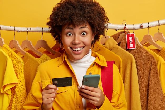 Zaskoczona Pozytywna Afroamerykanka Uśmiecha Się Szeroko, Korzysta Z Nowoczesnego Smartfona I Karty Kredytowej Darmowe Zdjęcia