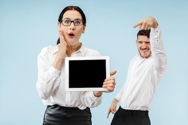 Zaskoczony Biznesmen I Kobieta Uśmiecha Się Na Niebieskiej ścianie I Pokazuje Pusty Ekran Laptopa Lub Tabletu Darmowe Zdjęcia