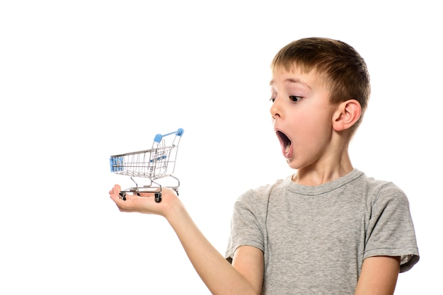 Zaskoczony chłopak z otwartymi ustami, trzymając na dłoni mały metalowy wózek na zakupy. izoluj na białym tle Premium Zdjęcia