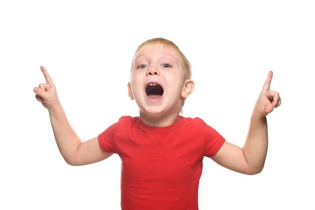 Zaskoczony Mały Blond Chłopiec W Czerwonej Koszulce Stoi I Wskazuje Palcami Wskazującymi W Górę Premium Zdjęcia