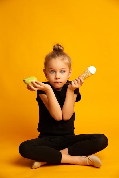 Zaskoczony Mały Tancerz Wybierając Gruszkę I Lody Premium Zdjęcia