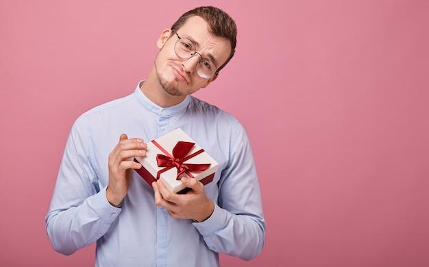 Zaskoczony mężczyzna w niebieskiej koszuli w czarnych okularach trzyma prezent w ręce Premium Zdjęcia