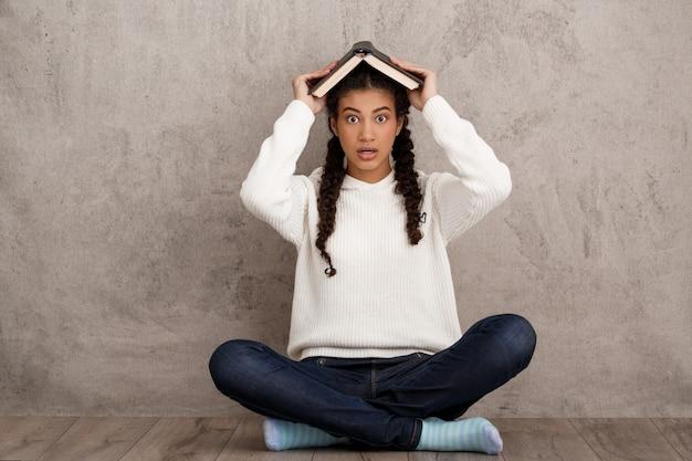 Zaskoczony, Młoda Kobieta, Trzymając Książkę Nad Głową Na Beżowej ścianie Darmowe Zdjęcia