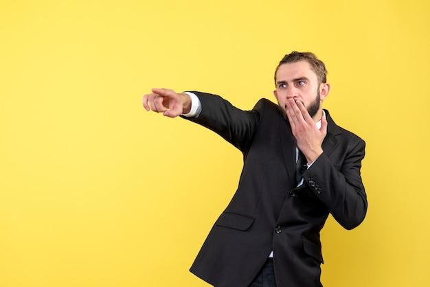 Zaskoczony Młody Człowiek Pokazujący Kierunek Na żółto Darmowe Zdjęcia