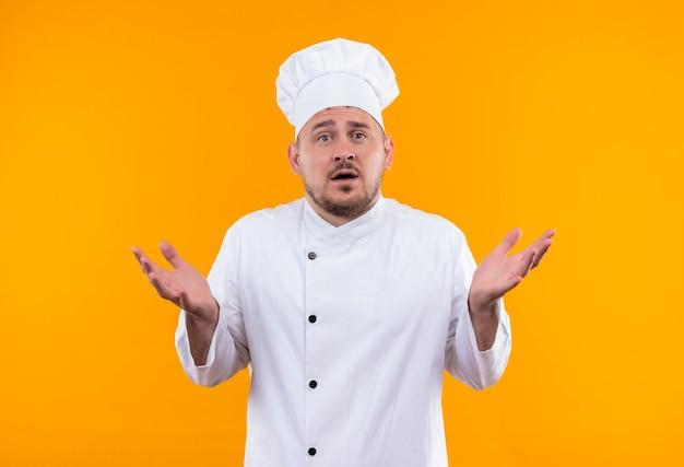 Zaskoczony, Młody Przystojny Kucharz W Mundurze Szefa Kuchni Pokazuje Puste Ręce Na Odizolowanej Pomarańczowej Przestrzeni Darmowe Zdjęcia