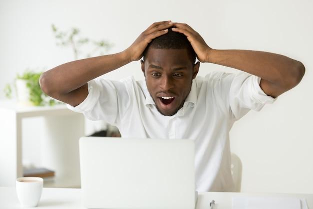 Zaskoczony podekscytowany człowiek african-american zaskoczony przez nieoczekiwane dobre wiadomości w internecie Darmowe Zdjęcia