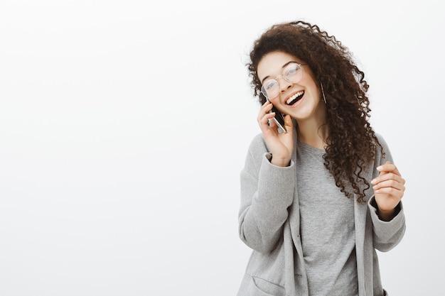 Zawsze Fajnie Z Tobą Rozmawiać. Pozytywna Szczęśliwa Młoda Europejska Fotografka W Stylowym Płaszczu I Okularach, śmiejąc Się Głośno Darmowe Zdjęcia