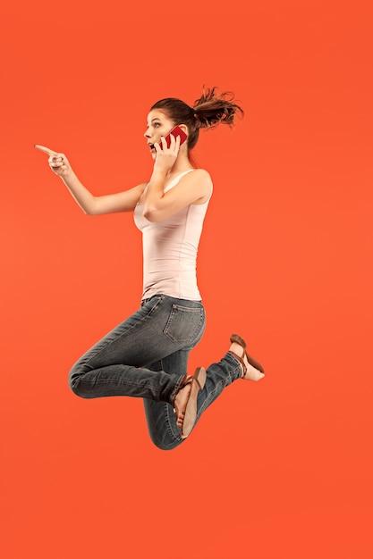 Zawsze Na Komórce. Pełna Długość Całkiem Młoda Kobieta Biorąc Telefon Podczas Skoków Na Czerwonym Tle Studio. Darmowe Zdjęcia
