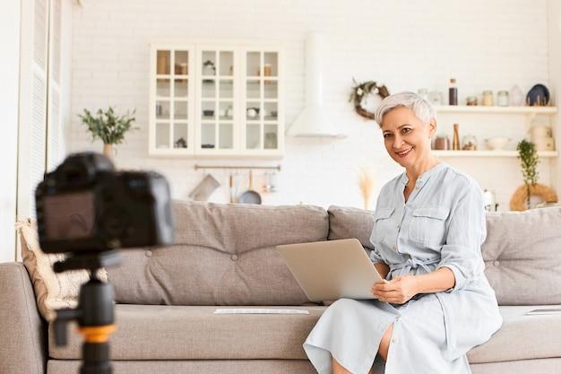 Zawsze W Kontakcie. Modna Elegancka Samozatrudniona Starsza Kobieta W Niebieskiej Sukience Siedząca Na Kanapie Z Przenośnym Komputerem Na Kolanach, Nagrywająca Wideo Na Blog, Opowiadająca Tajemnice Biznesowe, Wyglądająca Podekscytowana Darmowe Zdjęcia