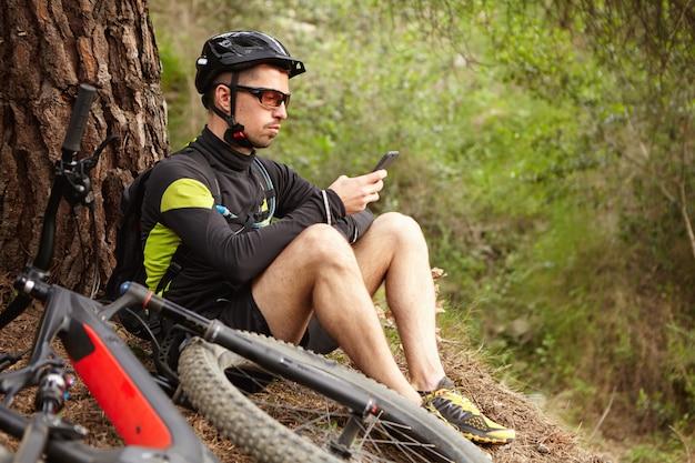 Zawsze W Kontakcie. Pewny Siebie Rowerzysta Piszący Wiadomość Lub Szukający Współrzędnych Gps Na Smartfonie, Siedzący Na Trawie Pod Dużym Drzewem Podczas Jazdy Na Rowerze Po Lesie, Jego E-rower Leżący Na Ziemi Obok Niego Darmowe Zdjęcia