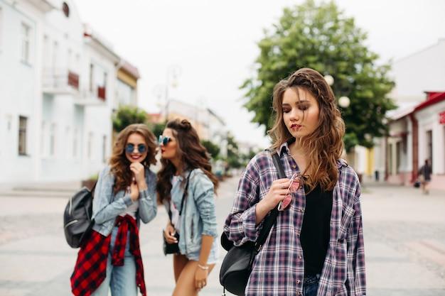 Zazdrosne dziewczyny szepczą o trzeciej dziewczynie przed kamerą. Premium Zdjęcia