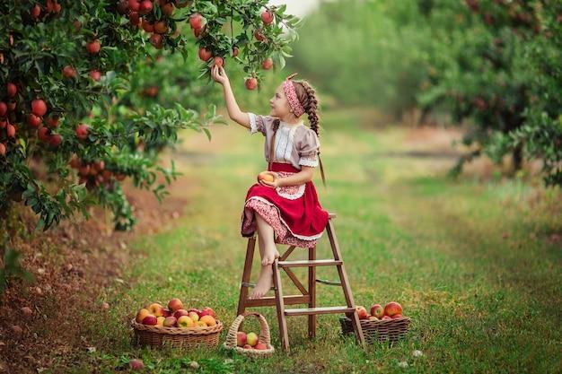 Zbieranie Jabłek Na Wsi W Ogrodzie. Piękna Dziewczyna W Strojach Vintage Czerwona Spódnica I Solokha Siedzi Obok Wiklinowych Koszy Z Jabłkami Premium Zdjęcia