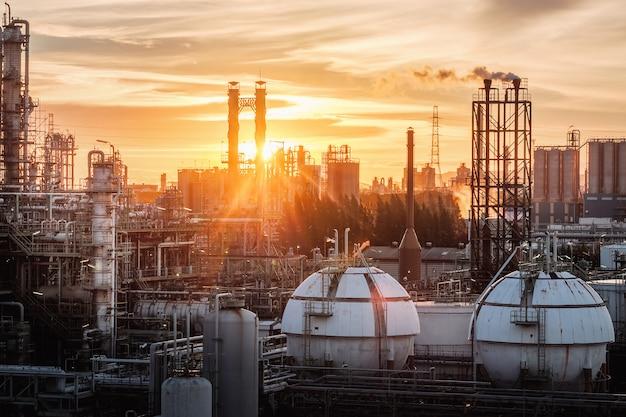 Zbiorniki Kulowe Do Przechowywania Gazu W Przemyśle Petrochemicznym Lub Rafinerii Ropy Naftowej I Gazu Wieczorem, Produkcja Zakładu Przemysłowego Ropy Naftowej Z Kolumną Gazową I Kominami Na Zachodzie Słońca Premium Zdjęcia