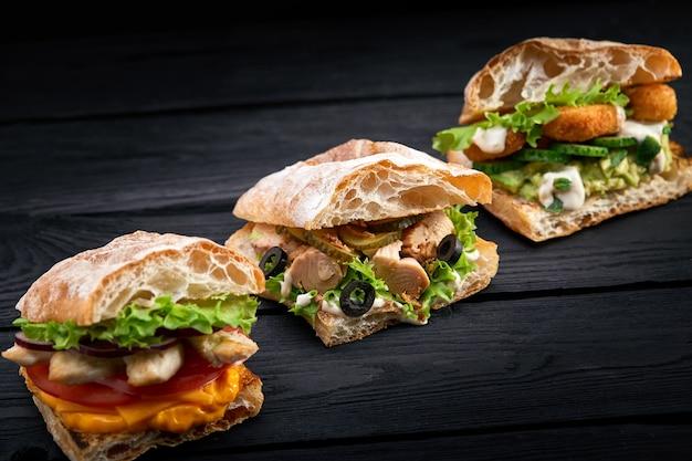 Zbliżenia Trzy Różne Apetyczne Kanapki Lub Hamburgery Na Drewnianej Powierzchni Premium Zdjęcia