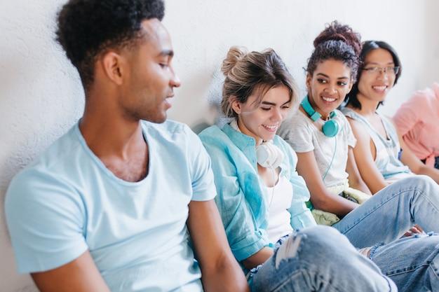 Zbliżenie Afrykańskiego Chłopca W Niebieskiej Koszuli Patrząc Na ładne Dziewczyny Nosi Spodnie Jeansowe. Portret Studentów Z Zainteresowaniem Opowiadających O Swoich Studiach. Darmowe Zdjęcia