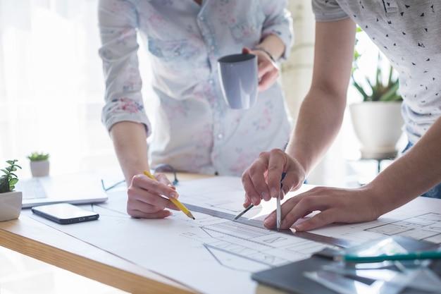 Zbliżenie architektury rąk do pracy nad planem na drewnianym stole w biurze Darmowe Zdjęcia