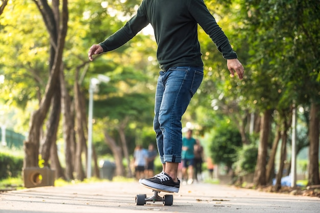 Zbliżenie Azjatycki Mężczyzna Gra Na Desce Surfingowej Lub Deskorolce W Parku Na świeżym Powietrzu Premium Zdjęcia