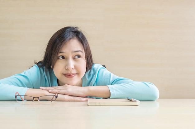 Zbliżenie azjatykcia kobieta kłamał na biurku z szczęśliwą twarzą w spoczynkowym czasie od czytać książkę Premium Zdjęcia