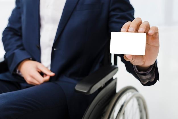 Zbliżenie: biznesmen siedzi na wózku inwalidzkim, pokazując białą wizytówkę Darmowe Zdjęcia