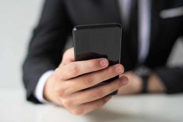 Zbliżenie biznesowego mężczyzna mienie i używać smartphone Darmowe Zdjęcia