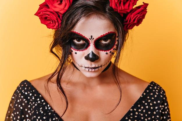 Zbliżenie Brązowookiej Kobiety Z Karnawałową Sztuką Twarzy. Meksykański Model Jest Zły, Patrząc Na Kamery Na Pomarańczowym Tle. Darmowe Zdjęcia