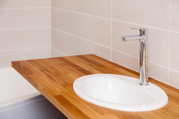 Zbliżenie brązowy tekowy drewniany pusty blat z białym okrągłym zlewem ceramicznym i wysokim srebrnym kranem. naprawa, remont łazienki w mieszkaniach, hotelu, spa Premium Zdjęcia
