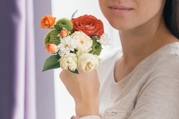Zbliżenie bukiet kwiatów w ręku młoda uśmiechnięta kobieta Premium Zdjęcia