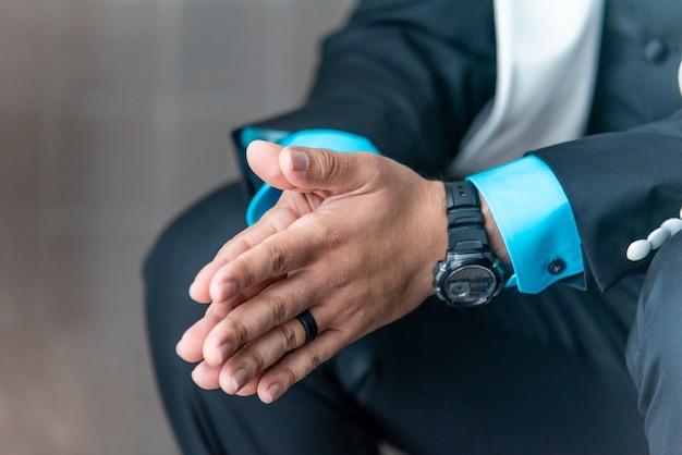 Zbliżenie Człowieka W Garniturze, Trzymając Ręce Razem Podczas Oczekiwania Darmowe Zdjęcia