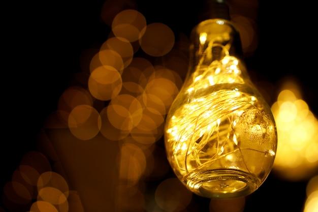 Zbliżenie dekoracyjny dowodzony światło w rocznik żarówce z włącznikiem na światłach jarzy się w nocy i rozmywa. Premium Zdjęcia