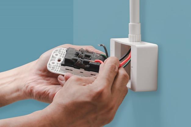 Zbliżenie Dłoni Elektryka Podłącza Przewód Zasilający Do Gniazdka Elektrycznego Premium Zdjęcia