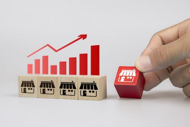 Zbliżenie Dłoni I Drewniane Kostki Zabawki Bloki Z Ikonami Sklepu Biznesowego Franczyzy Premium Zdjęcia