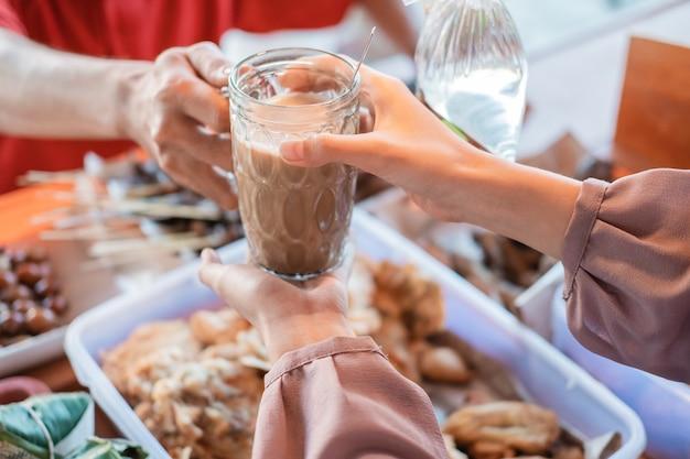 Zbliżenie Dłoni Kelnerki Stoiska Kobiet, Podając Szklankę Napoju Klientowi W Sklepie Premium Zdjęcia