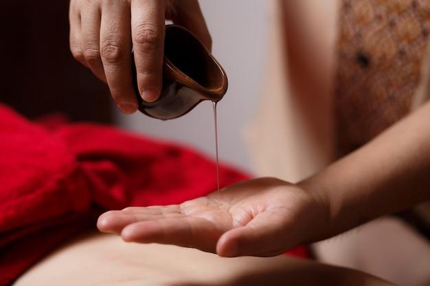 Zbliżenie Dłoni Masażysty Spływa Po Jego Dłoni Kropla Olejku Do Masażu Premium Zdjęcia