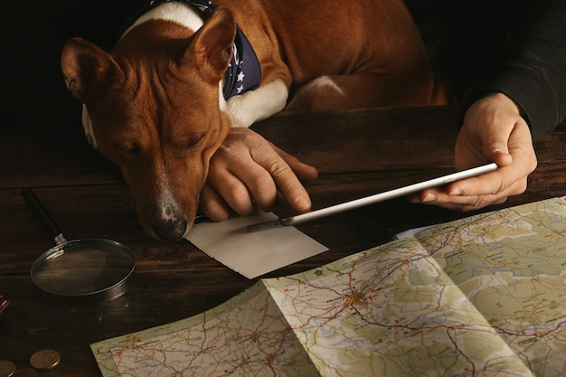 Zbliżenie Dłoni Mężczyzny Trzymającego Tablet I Przesuń Palcem, Planując Trasę Przygodową Na Wiekowym Drewnianym Stole, Podczas Gdy Ciekawy Pies Basenji Patrzy Na Niego łapami Na Blacie Darmowe Zdjęcia