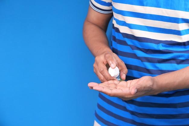 Zbliżenie Dłoni Młodego Człowieka Za Pomocą żelu Dezynfekującego Do Zapobiegania Wirusom. Premium Zdjęcia